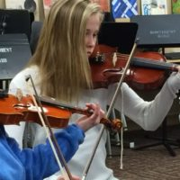 Two kids taking violin lessons